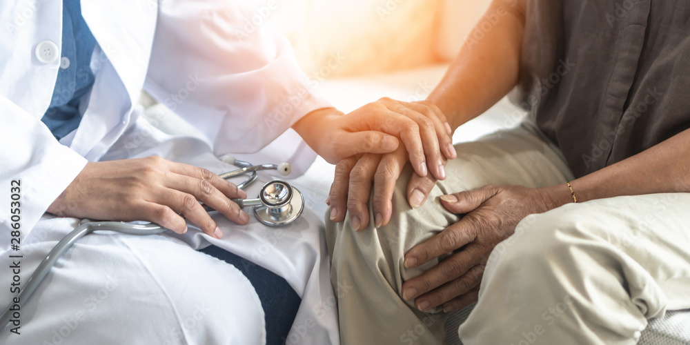 Fototapeta Parkinson's disease patient, Arthritis hand and knee pain or mental health care concept with geriatric doctor consulting examining elderly senior aged adult in medical exam clinic or hospital