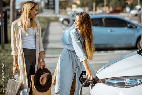 Woman plugging charging gun into the electric car on the parking outdoors, going Fototapeta