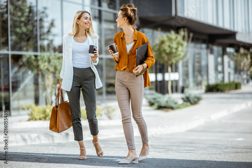 Photo sur Toile Les Textures Full body portrait of a two young businesswomen walking with coffee cups near the modern office building outdoors