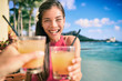 Leinwandbild Motiv Cocktail toast couple going out on beach restaurant cheering with rum mai tai drinks on Waikiki, Honolulu, Hawaii travel. Happy Asian woman holding glass of alcohol toasting with man.