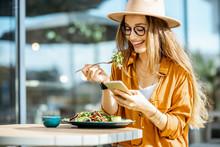 Stylish Young Woman Eating Hea...