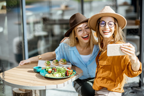 Fotomural  Two female best friends making selfie photo while sitting together on a restaura