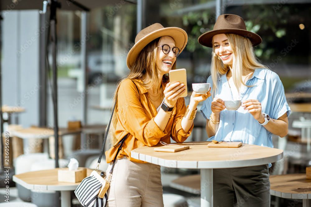 Fototapeta Two female best friends spending time together on the cafe terrace, feeling happy standing with coffee and phone during a summer day