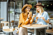 canvas print picture - Two female best friends spending time together on the cafe terrace, feeling happy standing with coffee and phone during a summer day