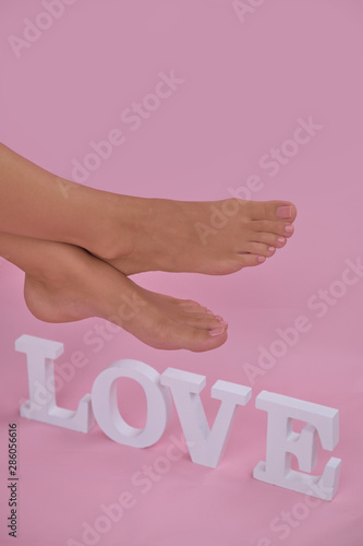 Perfectly made pedicure. Female legs on the pink background, inscription love.