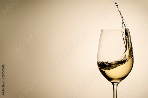 Keuken foto achterwand Alcohol Suspended drops and splash of white wine in glass