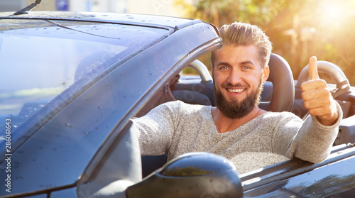 Young, friendly bearded business man is driving in luxury cabriolet car - 286061643