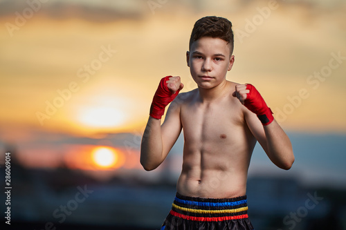 Photo  Young fighter training on the roof at sunset