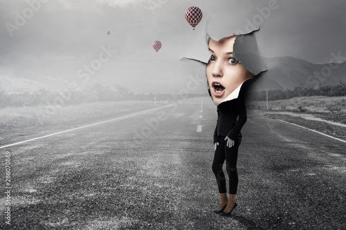 Photo  Woman looking out from a hole of torn paper