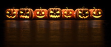 Seven Halloween Pumpkin Glowing Faces In A Row Isolated On Black Background. 3D Rendering Illustration