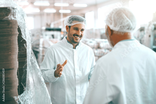 Two cheerful Caucasian food plant workers in white uniforms and with hairnets standing and talking about food production.