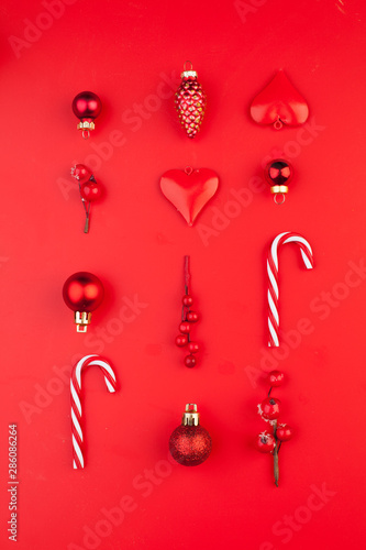 Merry Christmas composition with red baubles, holly berries, candy and cones on bright red background. Xmas flat lay top view