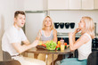 Friends sitting at table in kitchen
