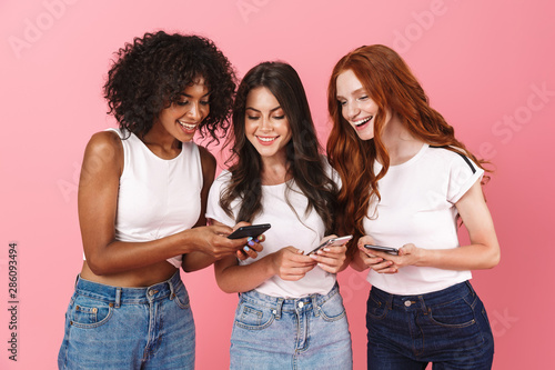 Smiling positive young three multiethnic girls friends posing isolated over pink wall background using mobile phones. - 286093494
