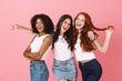 Cheery young three multiethnic girls friends posing isolated over pink wall background.