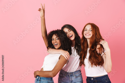 Fotografiet  Three cute young girlfriends wearing casual outfits standing