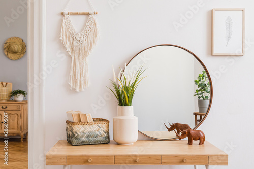 Fototapeta Sunny boho interiors of apartment with mirror, dressing table, furnitures, flowers, plants, rattan box, books, sculpture, macrame and design accessories. Stylish home decor of open space. Template. obraz