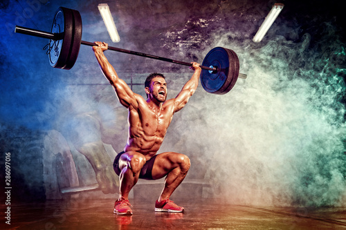 Storng Muscular Powerlifter Exercise With Heavy Barbell - 286097016