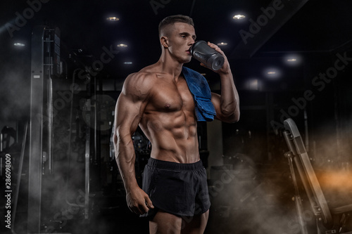 Fotografia  A young handsome man with big muscles, holds a shaker with protein, rest after c