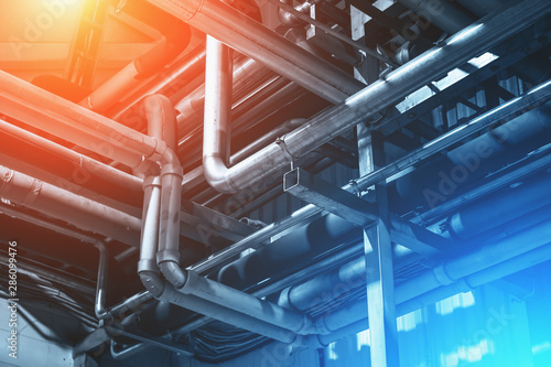 Fototapeta Industrial background with steel pipes or tubes of air ventilation system as abstract industry equipment in blue tones with red light obraz