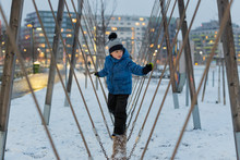 Young Boy Climbing And Holding Balance On A Snowy Playground In The Winter Time.