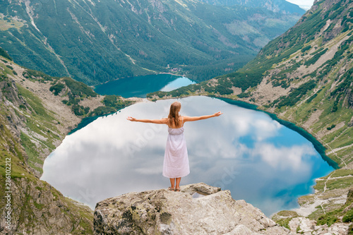 Türaufkleber Blau türkis Beautiful long haired girl in white dress standing with hands apart in Polish mountains with fabulous scenic view on background