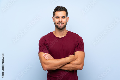 Handsome man over isolated blue background keeping the arms crossed in frontal p Tablou Canvas