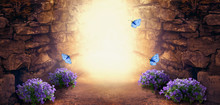 Photo Background With Magical Trail Leading Through Stone Dungeon Cave Towards Mystical Glow, Fantastic Bluebells Campanula Flowers, Flying Blue Butterflies. Fairytale Tranquil Fantasy Scene