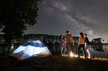 Night Camping On Lake Shore Near Campfire. Two Couple Having A Rest Together Near Illuminated Tent. Friends Enjoying View Of Night Sky Full Of Stars And Milky Way, Quiet Water Surface On Background.