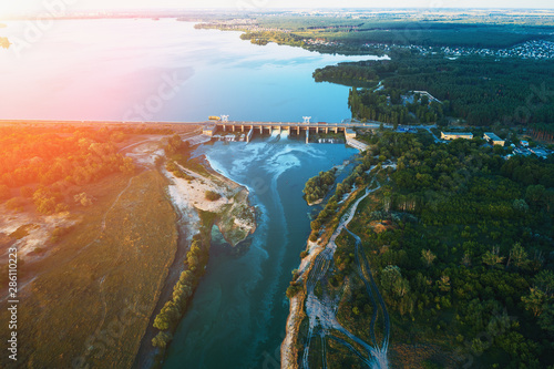 Fotografia  Aerial view of Dam at reservoir with flowing water at sunset, hydroelectricity p