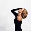 canvas print picture - Blonde woman young actress in black tight dress stands with her palm covering her face and head back and laughs