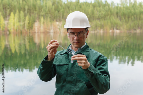 industrial ecologist takes a sample of water from lake at the site of a flooded Tablou Canvas