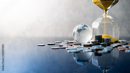 Fototapeta Global business investment growth. Wealth concept. Gold sand running through the shape of modern hourglass with world globe crystal glass and US dollar coins on blue reflective table. obraz