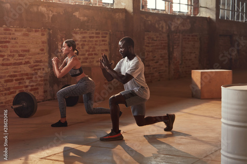 Sport couple doing leg lunge exercise workout at gym Wallpaper Mural