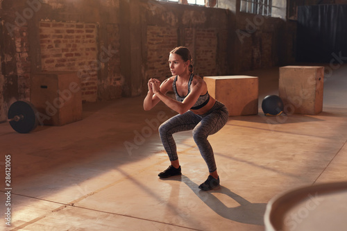 Foto  Fitness workout. Sport woman doing squat leg exercise at gym