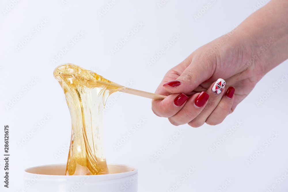 Fototapety, obrazy: Liquid yellow sugar paste or wax for depilation on a stick close-up on a white background
