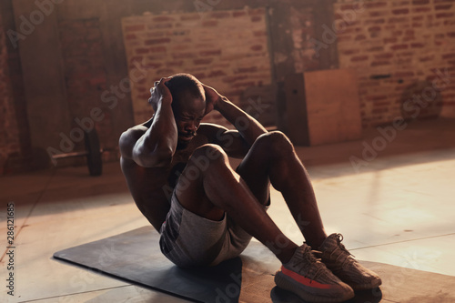 Fotomural  Sport man doing abs crunches exercise, fitness workout at gym