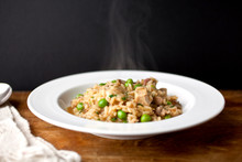 Close Up Of Risotto With Turkey, Mushrooms And Peas Served On Plate