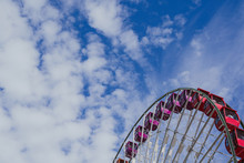 Negative Space, Artistic Composition Of A Colorful Large Ferris Wheel Against A Partly Cloudy Sky