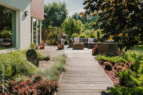 Fotografia, Obraz Wooden path to terrace in the garden with trendy garden furniture