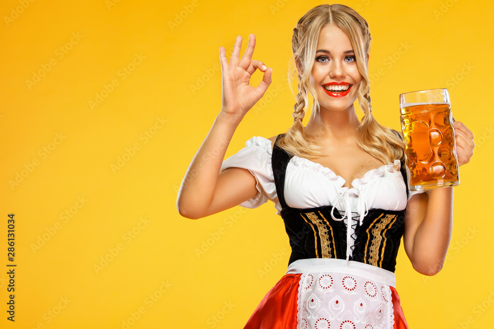 Fototapety, obrazy: Young sexy Oktoberfest girl waitress, wearing a traditional Bavarian or german dirndl, serving big beer mugs with drink isolated on yellow background. Woman showing ok sign with fingers.