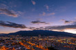 Cityscape of Quito city at sunset with the mighty peaks of the Pichincha volcano, Andes mountains, Ecuador.