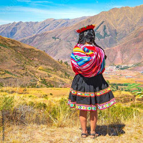 Kwadratowy format miejscowej damy keczua z tradycyjnym stylem włosów, suknią i kapeluszem, patrząc na pasmo górskie Andów w ruinach Inków w Tipon niedaleko Cusco w Peru.