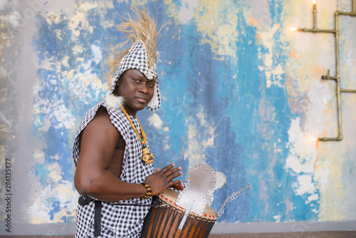 Fotografie, Obraz African artist in traditional clothes playing djembe drum
