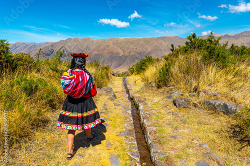 Fototapeta Young quechua indigenous woman walking along an inca aqueduct in the archaeological site of Tipon near the city of Cusco, Sacred Valley of the Inca, Peru