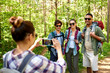 canvas print picture - travel, tourism and hike concept - group of friends with backpacks being photographed by woman with smartphone in forest