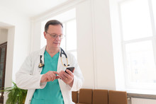 Doctor Using Smartphone On Corridor