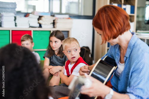 Fotografiet  A down-syndrome boy with school kids and teacher sitting in class, playing guitar