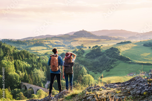 Foto Rear view of young tourist couple travellers hiking in nature, resting