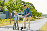 family, leisure and fatherhood concept - happy father spending time with little son riding scooters and making high five in city - 286145045